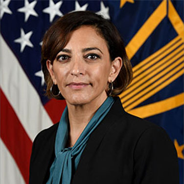 Image of Katie Arrington; Arrington has short brown hair and wears a dark suit with a teal scarf.