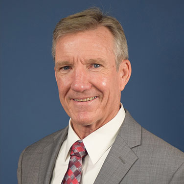 Image of Gen Hawk Carlisle, USAF (Ret) who wears a gray suit, has a red tie, is seated in front of a blue background, and smiles with his teeth showing.