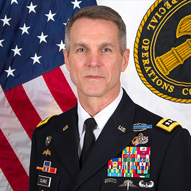 Image of Gen Richard Clarke, USA. A Man is seated in front of the U.S. flag and wears military uniform with many insignias and buttons. He has graying hair at the temples and a closed mouth smile.