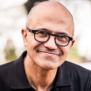 Image of Satya Nadella; a man with dark square glasses, no hair, and a closed mouth smile. He wears a black shirt.