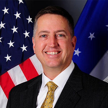 Image of Mr. James Smith, USSOCOM. Smith is seated in front of the U.S. flag and is wearing a dark suit, gold tie, and smiles with his teeth showing.