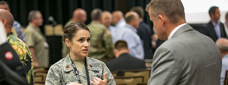 conversation between female military personnel and male industry personnel